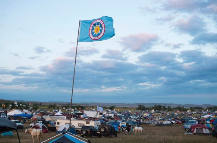 A Standing Rock Sioux flag flies over a protest encampment near Cannon Ball, North Dakota where members of the Standing Rock Sioux tribe and their supporters have gathered to voice their opposition to the Dakota Access oil Pipeline (DAPL), September 3, 2016. Drive on a state highway along the Missouri River, amid the rolling hills and wide prairies of North Dakota, and you'll come across a makeshift camp of Native Americans -- united by a common cause. Members of some 200 tribes have gathered here, many raising tribal flags that flap in the unforgiving wind. Some have been here since April, their numbers fluctuating between hundreds and thousands, in an unprecedented show of joint resistance to the nearly 1,200 mile-long Dakota Access oil pipeline. / AFP PHOTO / Robyn BECKROBYN BECK/AFP/Getty Images